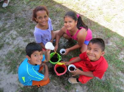 Children smiling holding cups with dirt