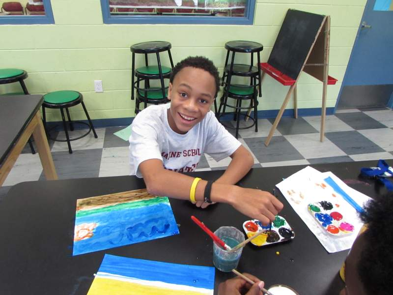 Young boy smiling while painting