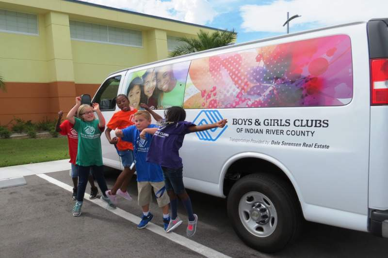 Children smiling and jumping in front of BGCIRC van